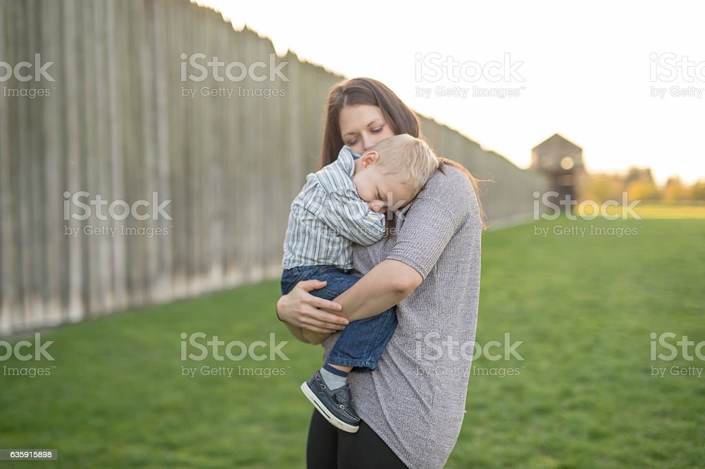 Mother holding sleepy young son in early morning light stock photo