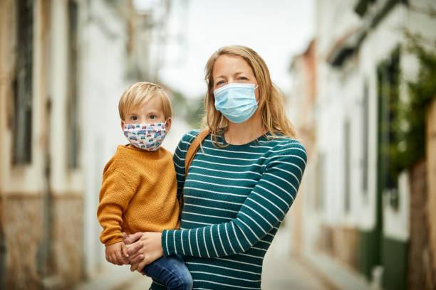 Mutter hält Sohn in armen auf der Straße mit Gesichtsmasken für COVID-19 – Foto