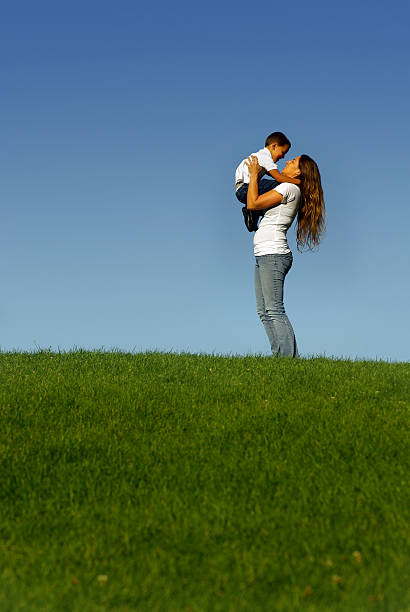 mother holding son on grassy green hill - mikefahl stock pictures, royalty-free photos & images