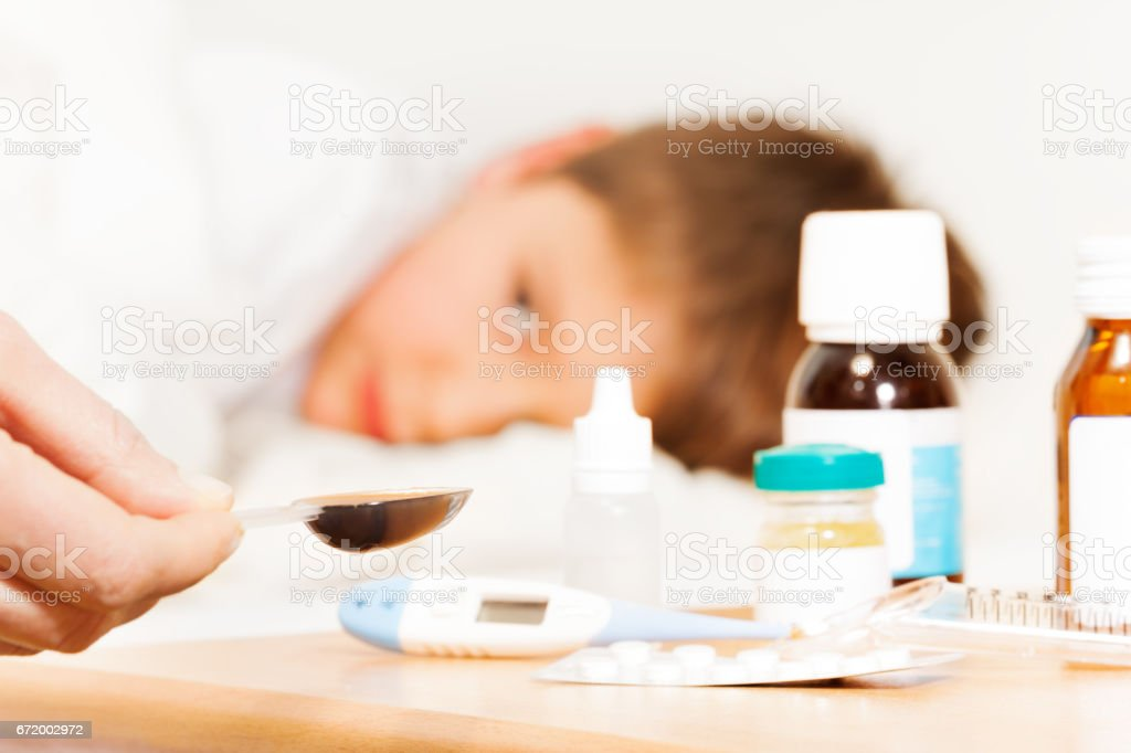 Mother holding spoon with meds for sick kid boy stock photo