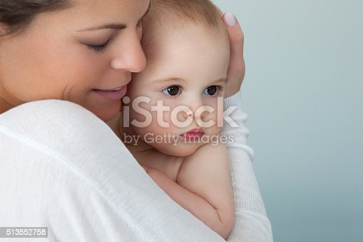 istock Mother Holding Tight Her Baby Boy On Blue Background 513552758