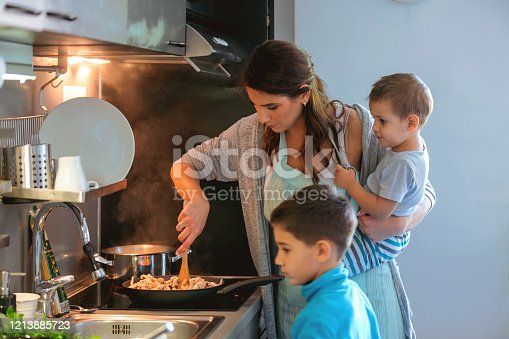 Single mother by the stove with toddler on hip, stirring mushrooms, her older son is standing by