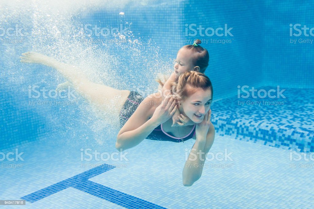 Mother holds baby, daughter learn to swim on swimming lesson, doing...