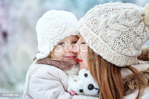 istock Mother holds daughter on hands in winter forest 470489169
