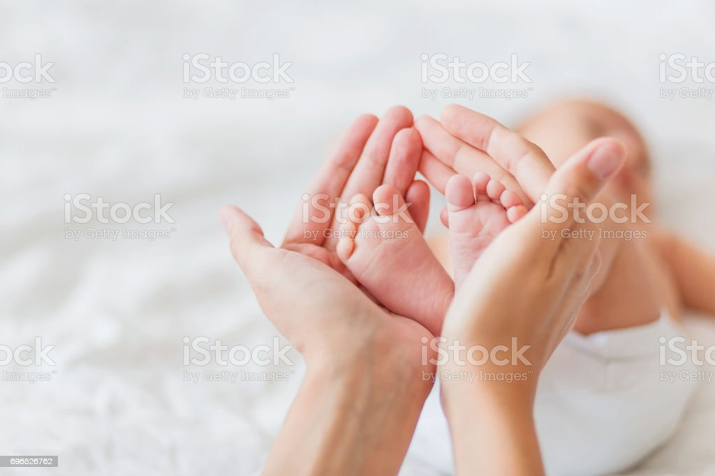 Mother holds newborn baby's bare feet. Tiny feet in woman's hand. Cozy morning at home. – zdjęcie