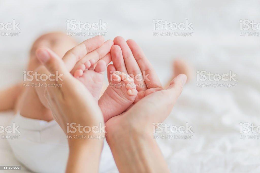 Anne, yeni doğan bebeğin çıplak ayak tutar. Kadın eli küçük ayaklarda. Rahat sabah evde. stok fotoğrafı