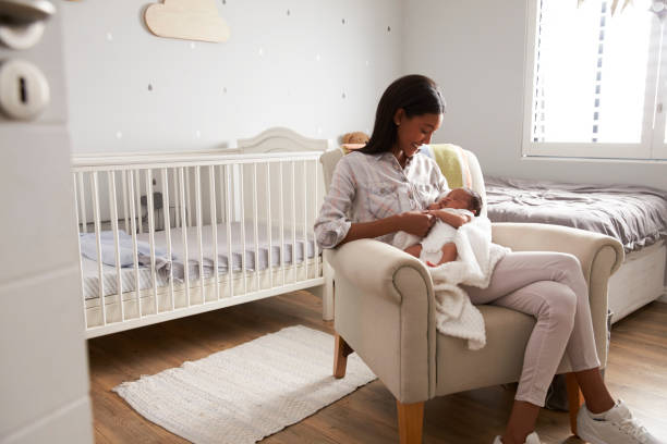 Mother Home from Hospital With Newborn Baby In Nursery stock photo