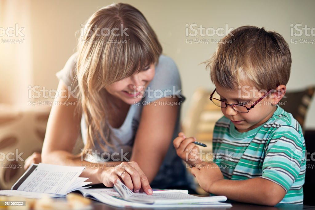 Mother homeschooling her son stock photo