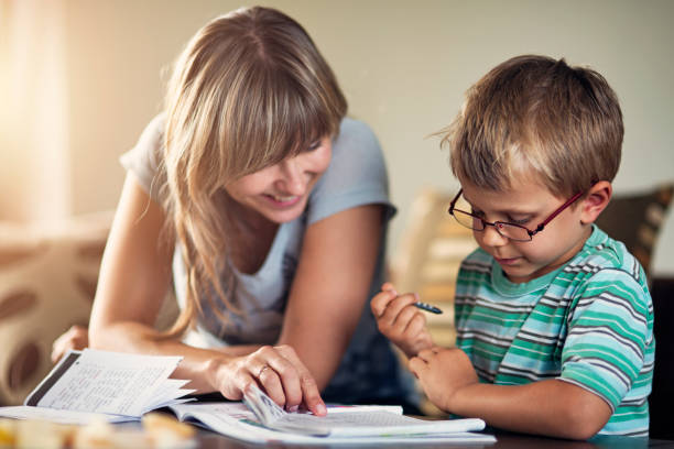 mother homeschooling her son - homework stock photos and pictures