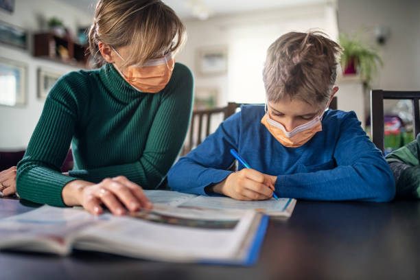 Mother homeschooling her son wearing face masks stock photo