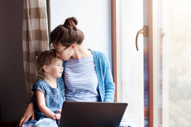 Mother hug and kiss daughter. Working mom works from home office. stock photo
