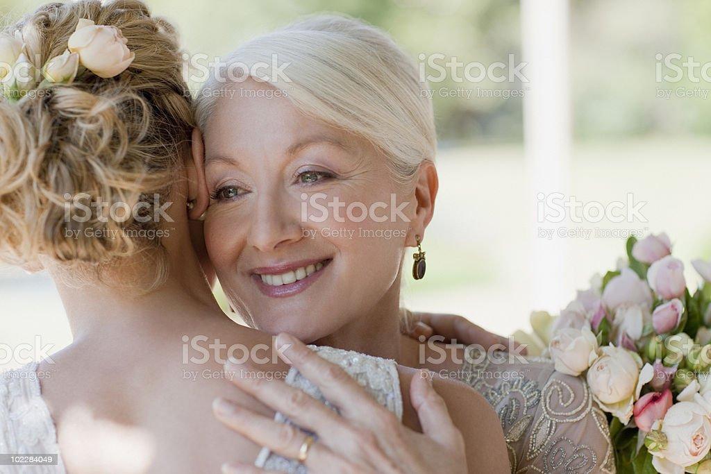 Mother hugging bride stock photo