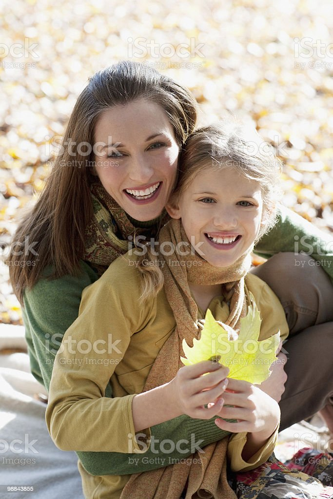 Mother hugging daughter holding autumn leaf royalty-free stock photo