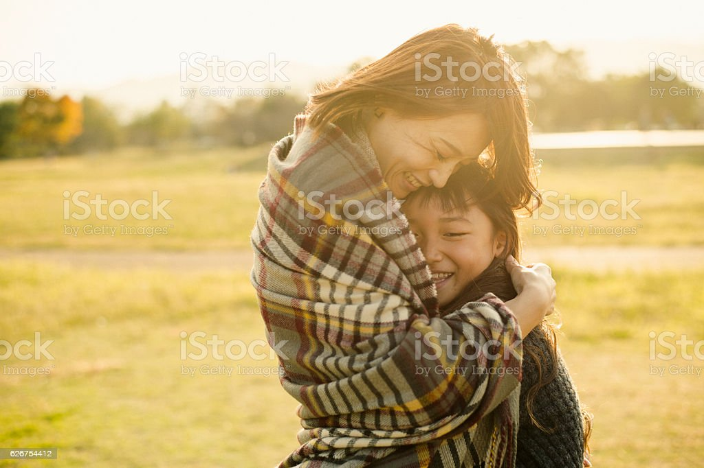 Mother hugging daughter in outdoors - Photo