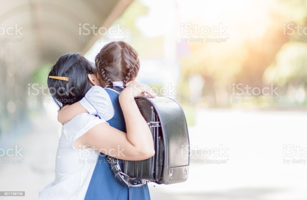 mother hugging daughter in uniform student royalty-free stock photo