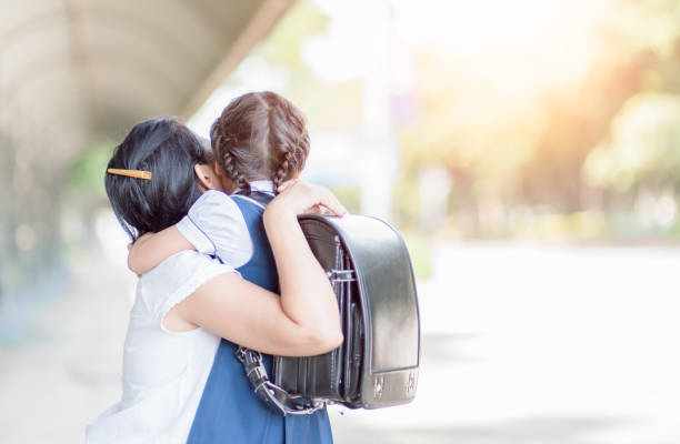 mother hugging daughter in uniform student stock photo