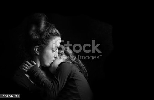 Touching Heart Felt Black and White Image of Mother Hugging and Nuzzling Young Daughter Tenderly with Dark Background with Copy Space