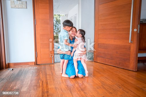 670900812istockphoto Mother hugging her children when coming home 968062706