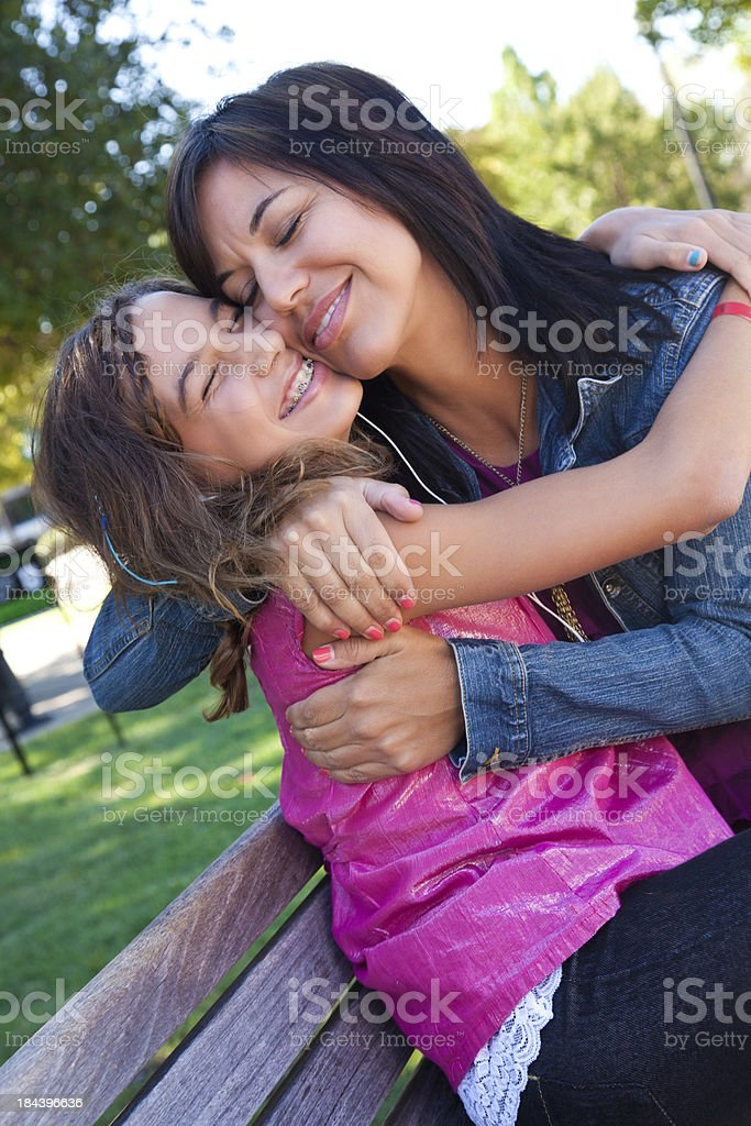 Mother hugging her teenage daughter on a park bench royalty-free stock photo