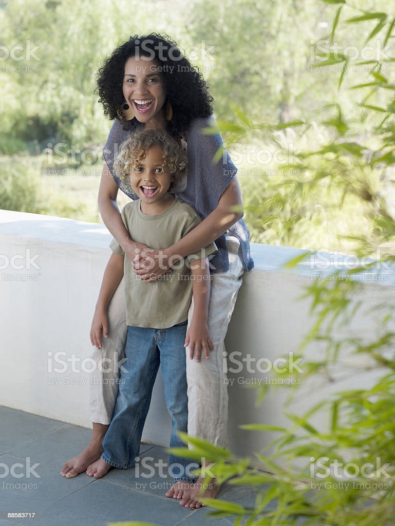 Mother hugging son on patio royalty-free stock photo