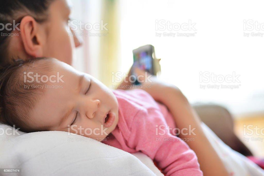 Mutter im Bett mit Baby-Tochter, die Handy  – Foto