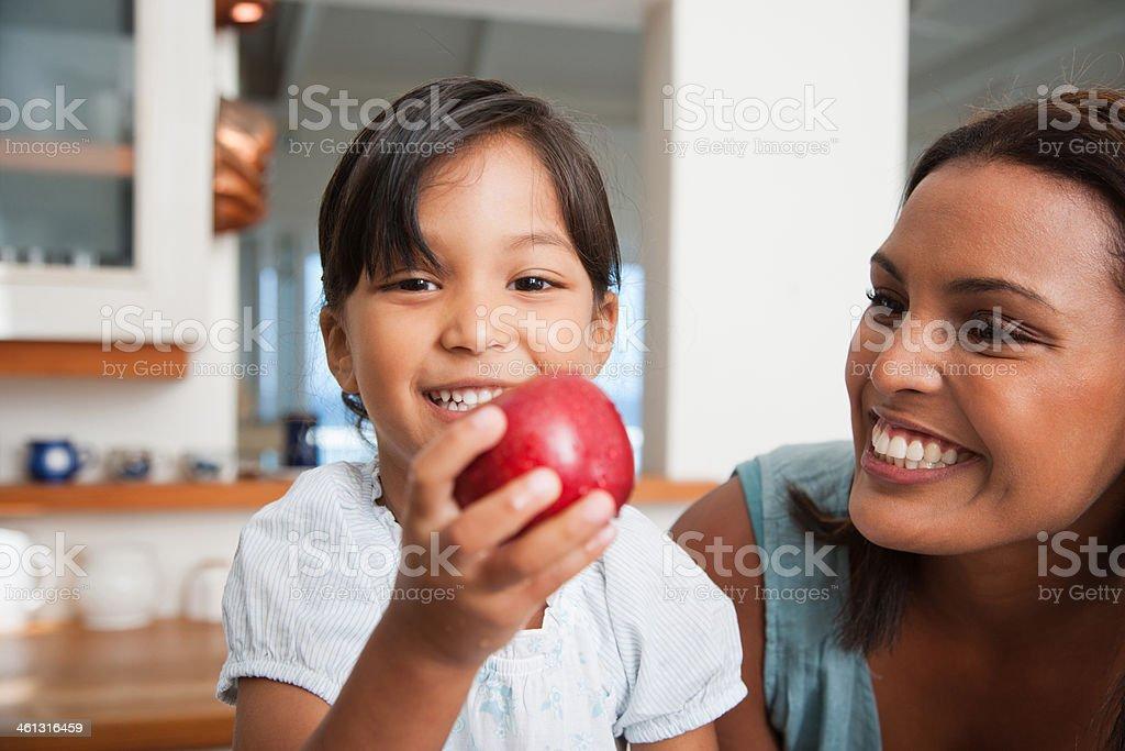 Mutter in der Küche mit Tochter holding roten Apfel – Foto