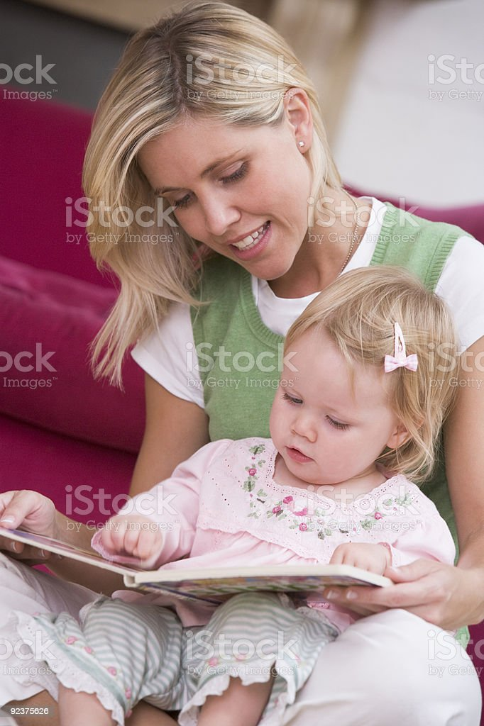 Mother in living room reading book with baby royalty-free stock photo