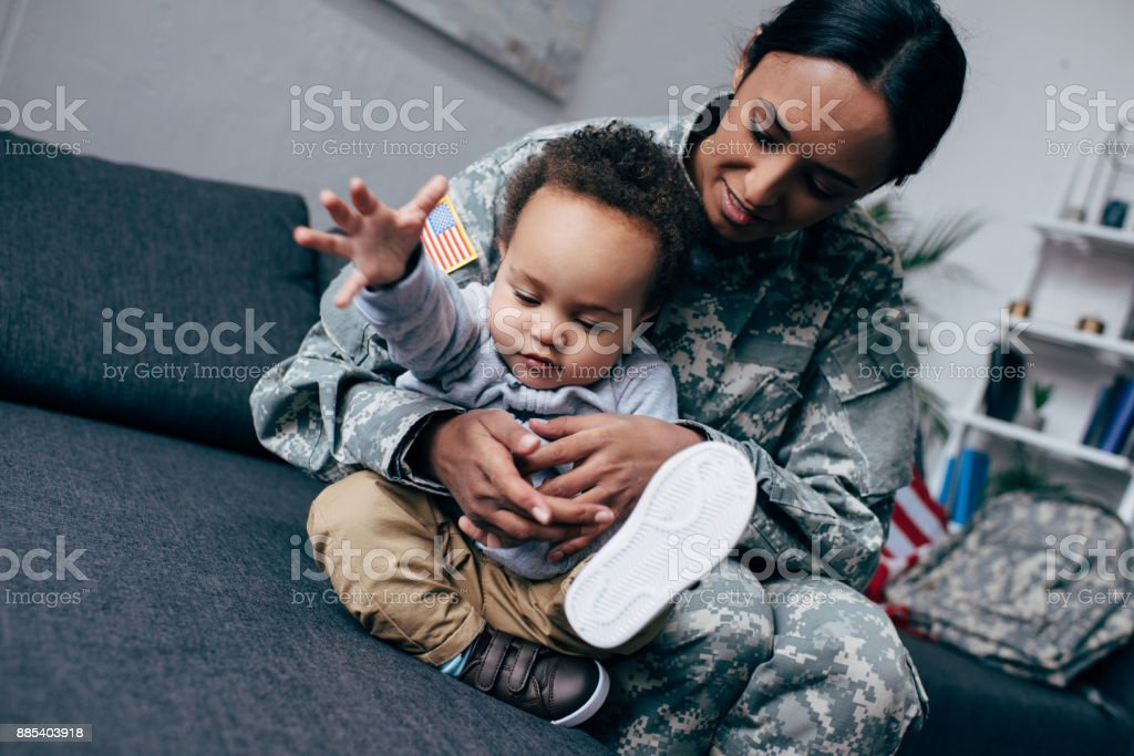 mother in military uniform with little son stock photo