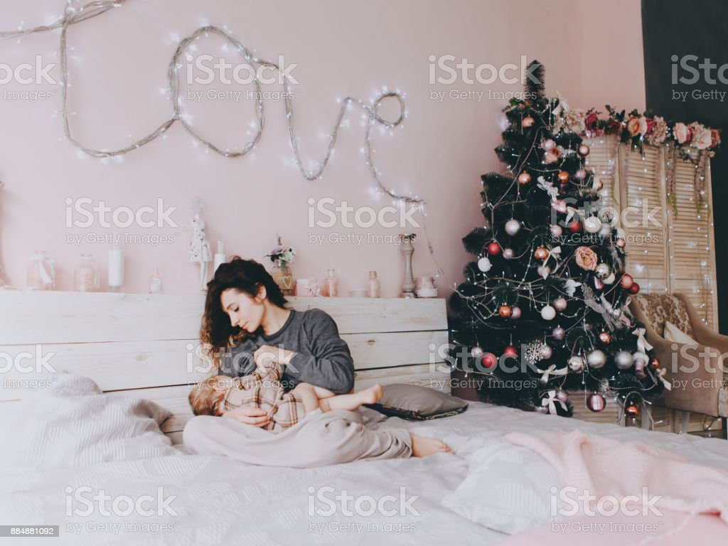 Mother is breast-feeding her daughter. Christmas. stock photo