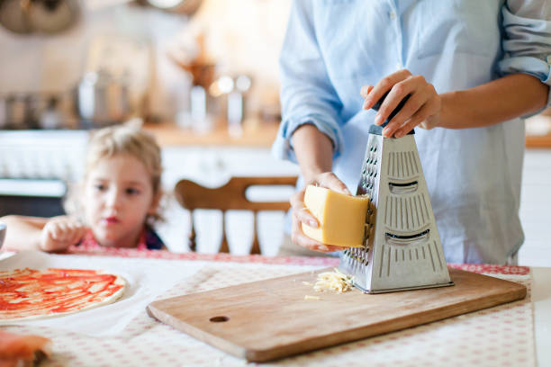 Mother is cooking with child. Woman grates cheese with grinder. Family is preparing pizza and homemade italian food in kitchen. Lifestyle, authentic, candid moment. stock photo