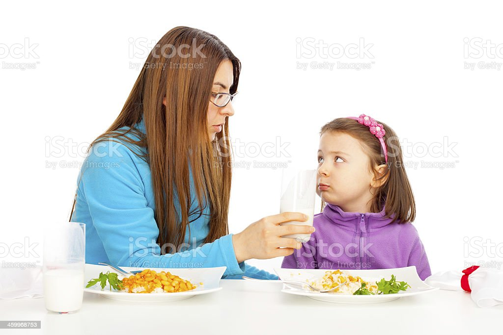 Mother is feeding her daughter stock photo