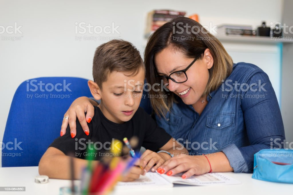 Mother is helping her son to finish his homework stock photo