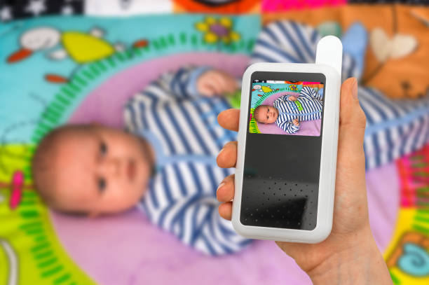 Mother is holding baby monitor camera for safety of her baby stock photo