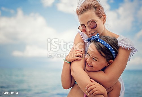 604367022 istock photo Mother is hugging her beloved daughter on the beach 848868104