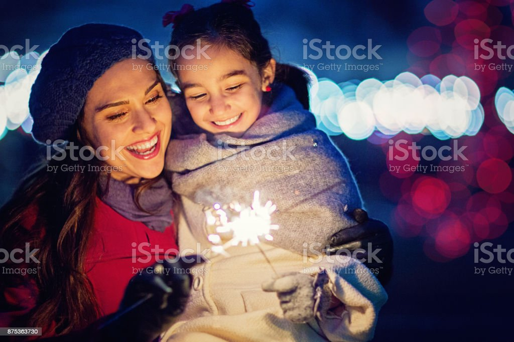 Mother is hugging her daughter at Christmas stock photo