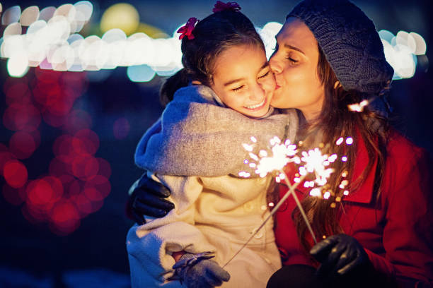 Mother is kissing her daughter at Christmas stock photo