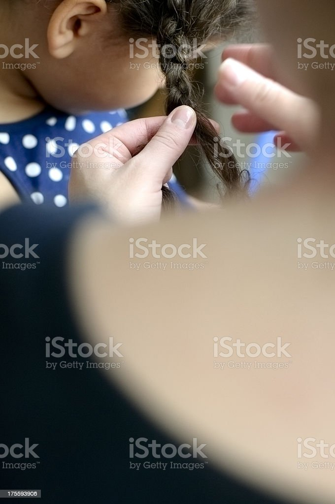 Mother is Making Braids to Her Daughter stock photo