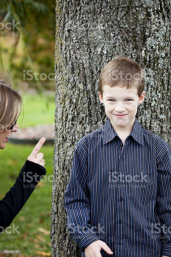 Mother is scolding son with smirky grin royalty-free stock photo