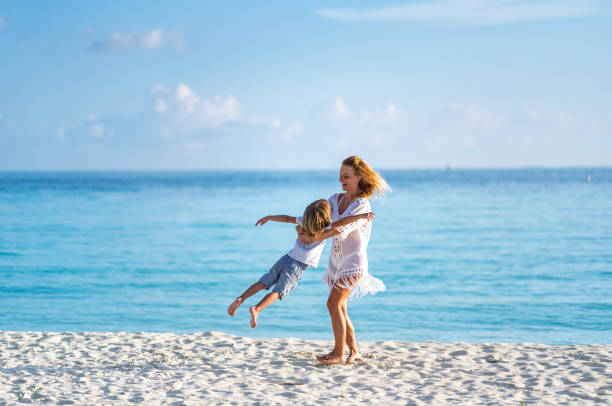 Mother is spinning son on beach stock photo