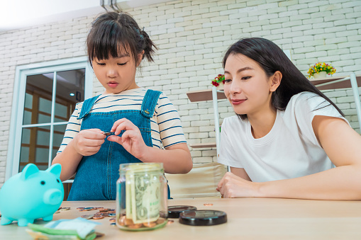 Mother is teaching daugther on financial saving and planing using saving jar and piggy bank with real moner, for Money and wealth education concept.