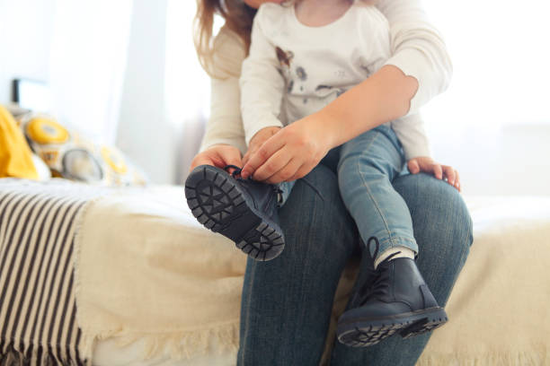 Mother is tying a shoe of a child stock photo