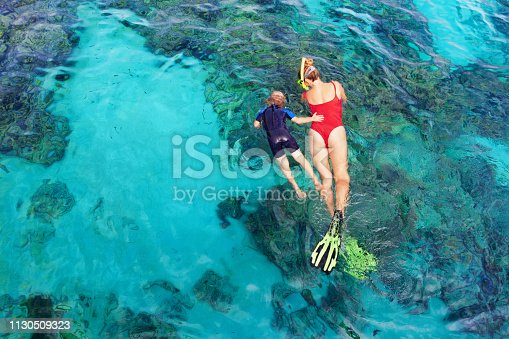 831127716 istock photo Mother, kid in snorkeling mask dive underwater with tropical fishes 1130509323