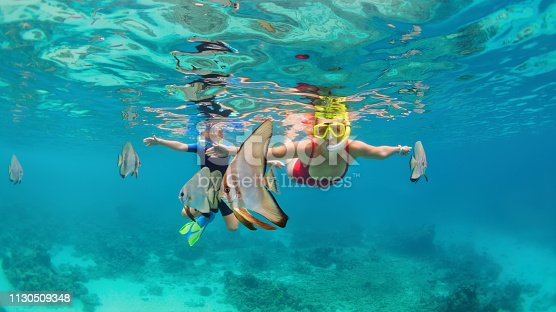 Happy family - mother, kid in snorkeling mask dive underwater, explore tropical fishes Platax ( Batfish). Travel lifestyle, beach adventure, swimming activity on summer with child. Focus on fishes