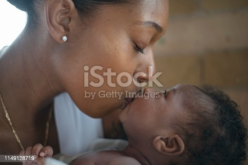A young mother affectionately kisses her newborn son on the lips. She has her eyes closed and is treasuring the moment.