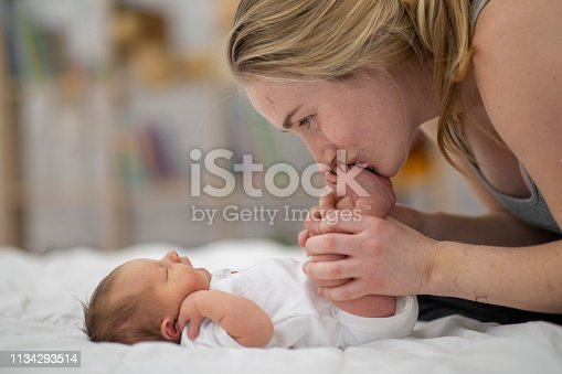 A caucasian mother smiles as she kisses her newborn baby's toes,  as the baby lies sleeping on a bed.