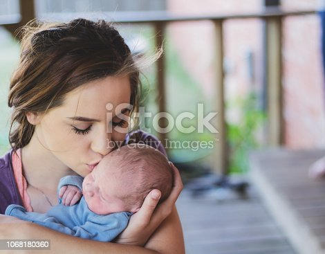 909771884 istock photo Mother kisses newborn son on the cheek as she holds him 1068180360