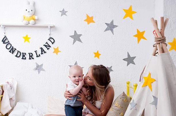 mutter küssen ein kind vor der schlafenszeit - tipi bett stock-fotos und bilder