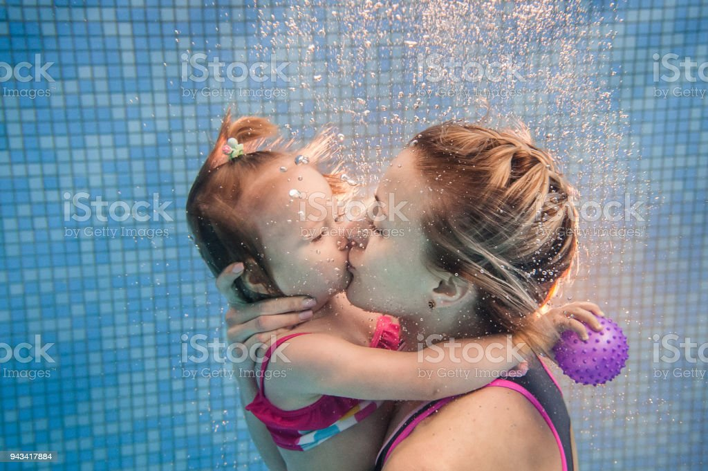 Mother kissing baby daughter learn to swim on swimming lesson, doing...