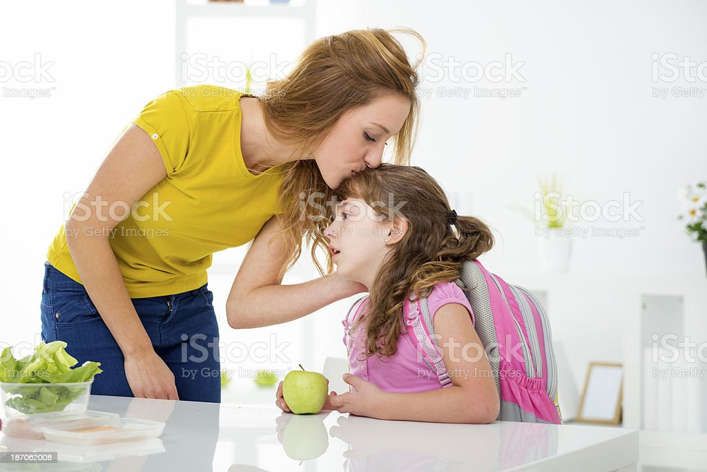 Mother kissing daughter before school. royalty-free stock photo