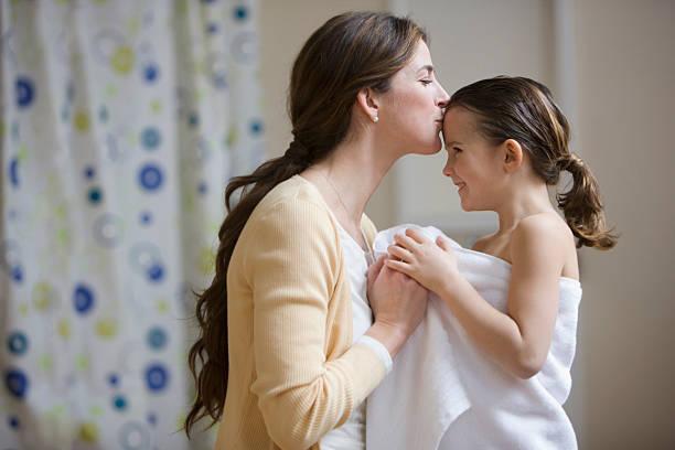 mutter küssen tochter die stirn nach bad - kinderbadewanne stock-fotos und bilder